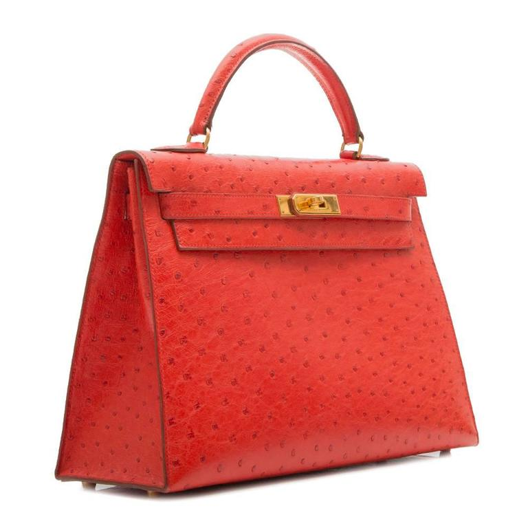 Hermès vintage Rouge Vif 32cm Kelly bag in ostrich leather featuring gold plated hardware. The interior of the bag is lined in matching goat leather with one zipped and two open pockets.  This bag comes with its strap, lock and key, protective felt