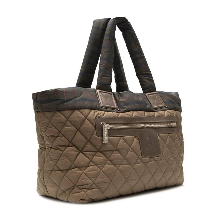 This Chanel Coco Cocoon tote bag showcases a spacious, lightweight khaki fabric with a Scottish flair. It opens to a roomy interior with side zip and FOB for your keys, perfect for daily essentials. A stand-out, chic tote made for light travels.