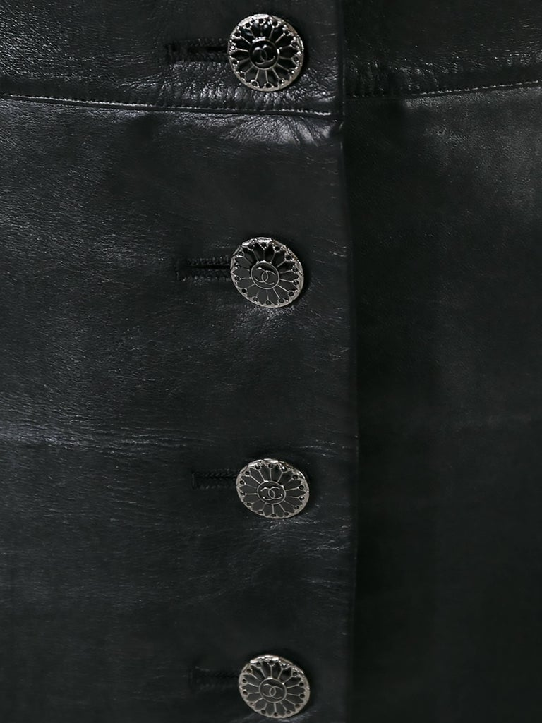 Perfect for adding tough-luxe to a look, this Chanel black leather mini skirt features a button-down front, finished with metallic monogram medallions. It has two side pockets and a black silk lining.  Colour: Black  Composition: Outer: 100%