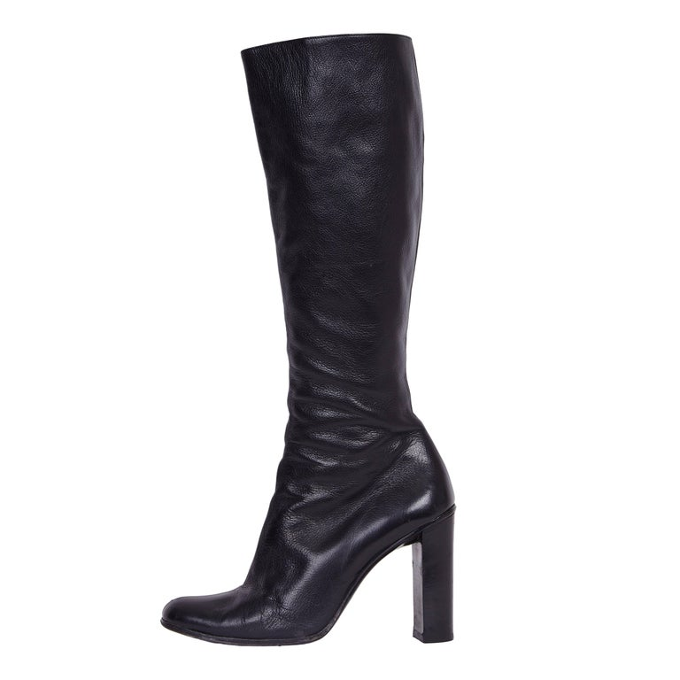 Exude the cosmopolitan appeal of Tom Ford's Gucci with this pair of knee-high leather boots, circa 1999. In a sleek silhouette, these Gucci boots are crafted in black leather, finished with a block heel, side zipper and a prominent monogram in