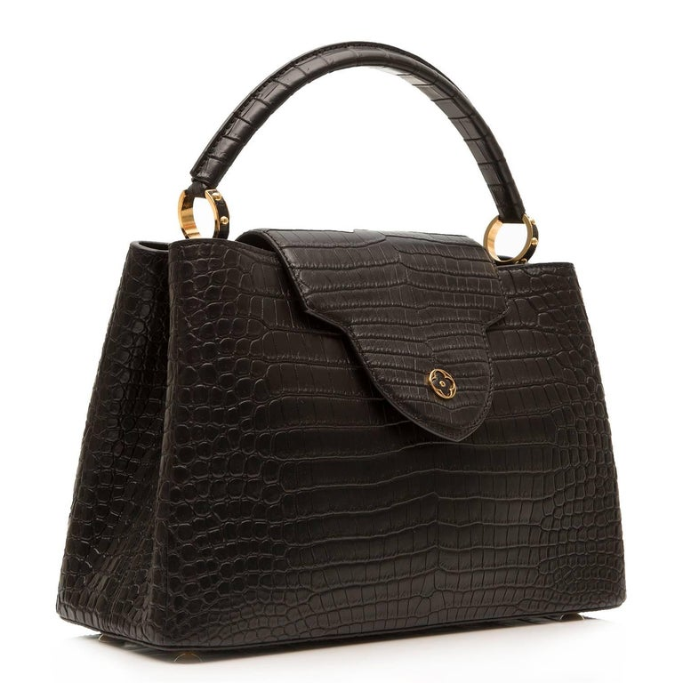 This exquisite Louis Vuitton Capucines bag takes its name from the rue des Capucines in Paris, where Louis Vuitton opened his first store in 1854. Crafted in the rare and precious Porosus crocodile skin, it combines refined details, including a