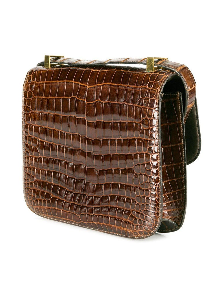 This extremely rare, vintage crocodile Hermès Constance bag comes in a unique and extremely sought after Miel Brown colour. The interior features one spacious interior compartment, containing one wide open slip pocket and one wide pocket with a