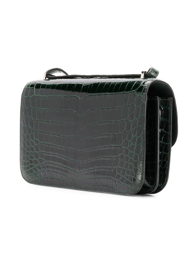 This 25cm Constance Elan shoulder bag from Hermès was meticulously crafted in France from a highly precious Niloticus crocodile in a deep shade of forest green. Offset with silver-tone palladium-plated hardware, its slender body is adorned with the