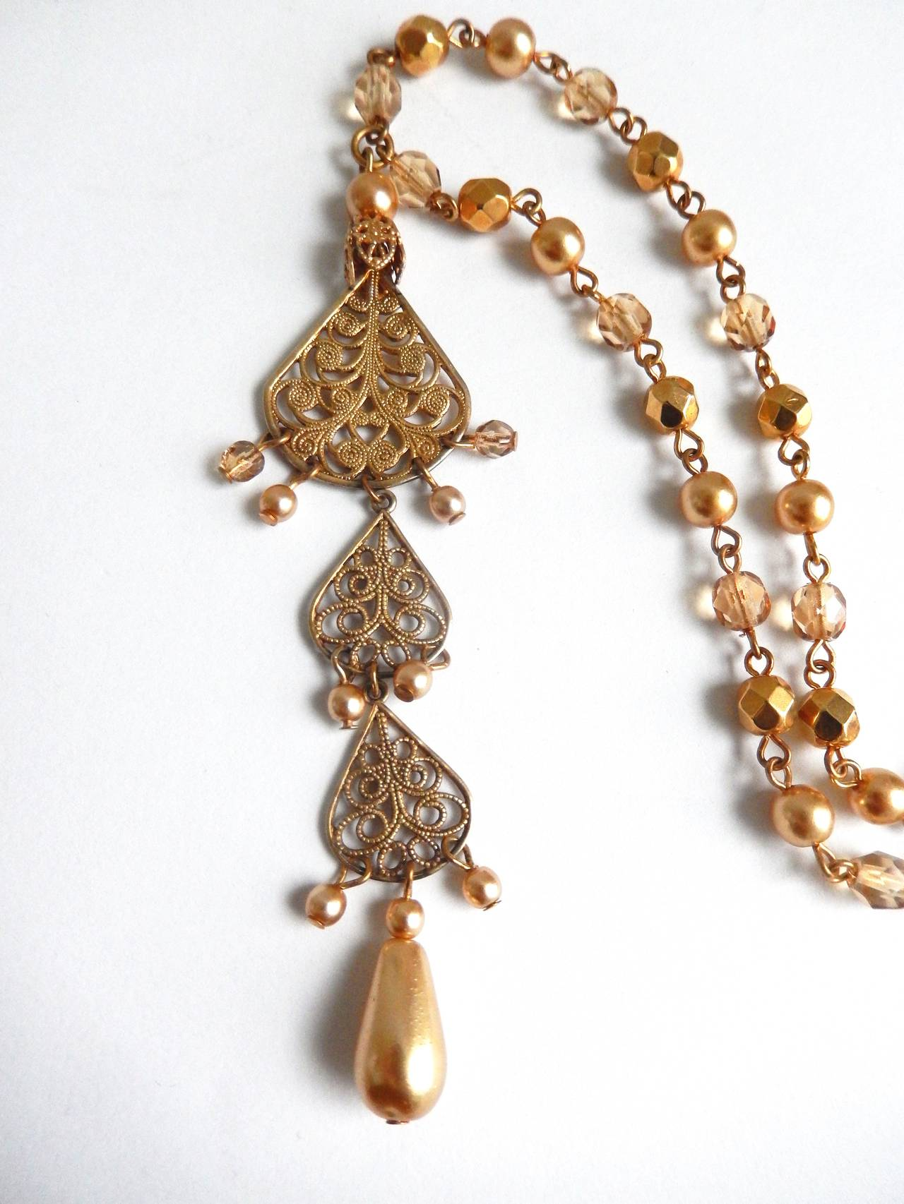 Miriam Haskell combines gilt metal medallions with citrine colored pearls and  gold faceted beads to create a delicate and sophisticated necklace.  The pearl pendant is approximately 4 inches in length.  A perfect summer necklace.