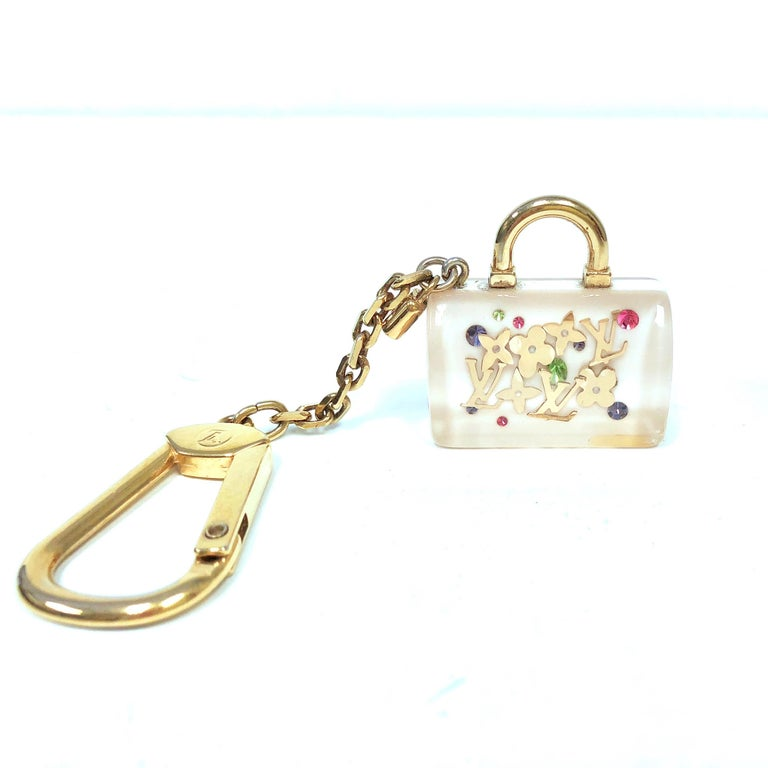 This Louis Vuitton white Speedy Inclusion charm features a white and clear resin Speedy bag with goldtone monogram logos and quatrefoils. The chain can be clipped on most metallic links on handbags or used as a key holder.  Measurements: 4.5