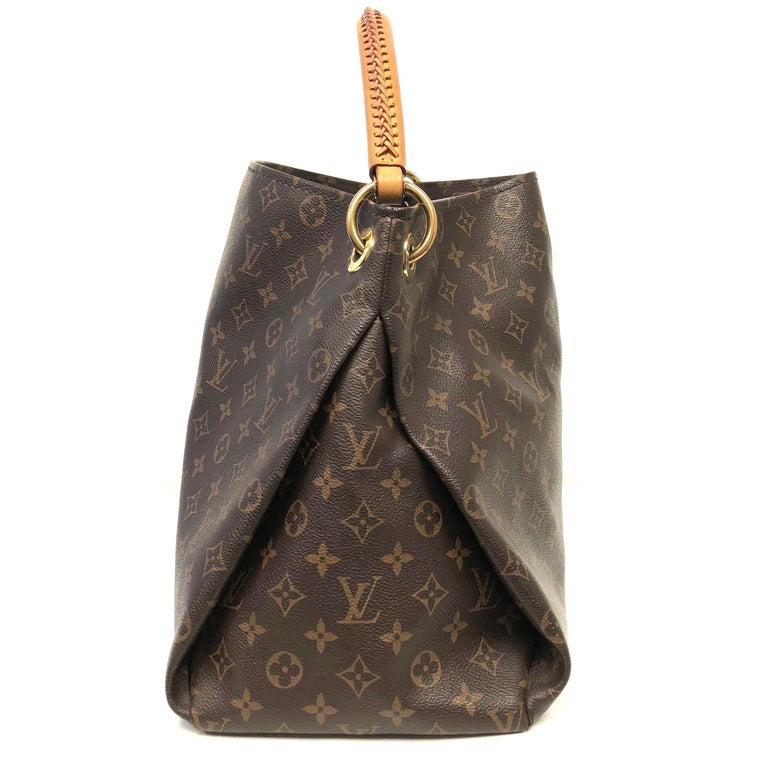 Crafted from Louis Vuitton's iconic brown monogram coated canvas, the bag features a rolled leather handle with braided detailing, protective base studs and gold-tone hardware accents. The bag opens to a beige microfiber interior with a long zipped
