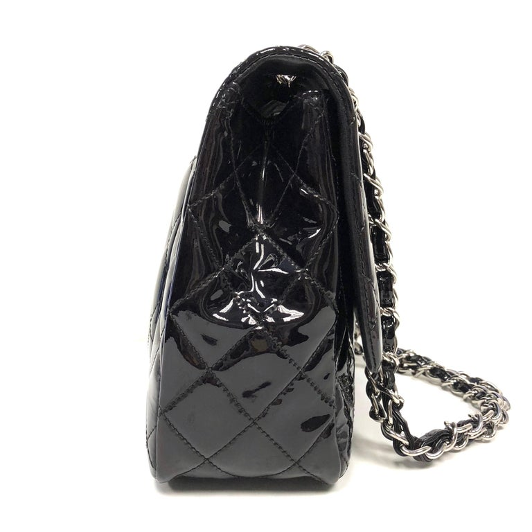Chanel Classic single flap bag, crafted of fine diamond quilted glossy patent leather in black. The bag features patent leather threaded silver chain shoulder straps and a facing half flap with a silver Chanel CC turn lock. The interior features
