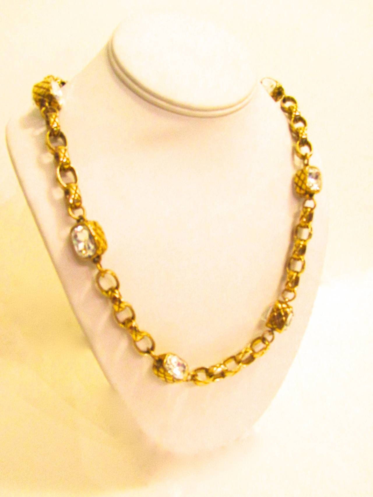 Rare 1980's Chanel gold-toned necklace with matelasse pattern engraved onto chain. Strass faceted crystals inlayed throughout the chain. Clear logo engraved onto one of the links of the chain. 
