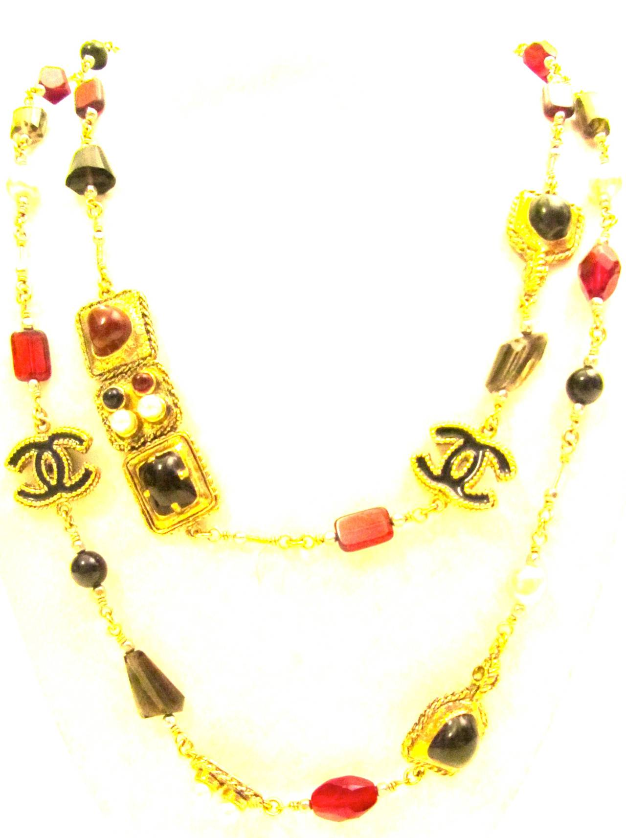 New Chanel necklace. Gold tone chain with faux pearls and alternating ornate gripoix stone inlay. Red, black, and gray gripoix stones. Black and gold CC logos on necklace. Rare and gorgeous necklace that is versatile for various occasions.