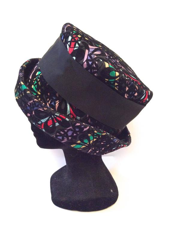 This fabulous multi-colored wide brimmed hat is from the late 1950's, early 1960's. It is in excellent condition. The hat encompasses a multi-colored striped background layered with black felt. Floral, geometric design. The beautiful underlying
