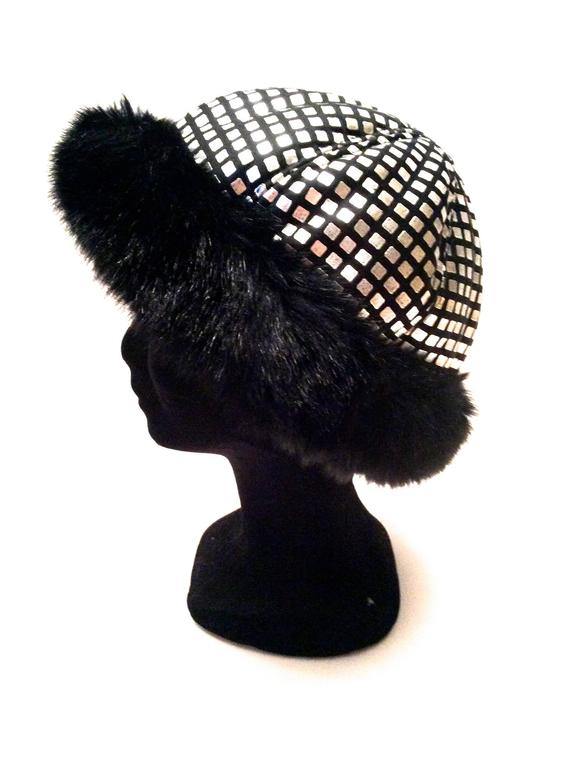 This is a fabulous example of a 1960's mod hat in excellent condition. The hat consists of 2.5 inch trim of faux fur and the overall fabric of the hat are little squares of metallic silk leather on a black background. Hat is made in France.   The