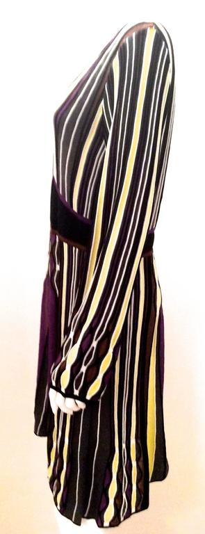 Presented here is a magnificent dress from Missoni. The dress is a series of vertical yellow, gray, black, purple, and brown lines of different sizings with a thick horizontal black line around the waist. The dress has long sleeves. There is a V