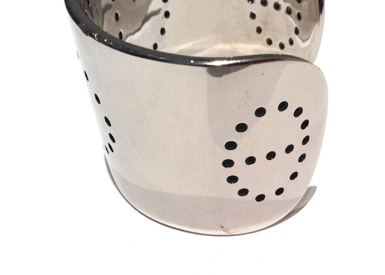 Presented here is an Hermes Eclipse cuff bracelet. The bracelet is solid sterling silver throughout. The bracelet has the classic perforated 'H' on the center of the cuff. There are two perforated circles on either end of the cuff as well. The total