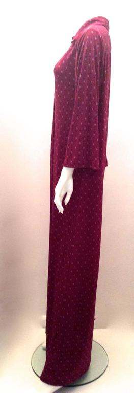 Presented here is a gorgeous vintage Christian Dior Maxi Day Dress. The dress is from the Miss Dior line. The dress is from the 1970's. The dress has a maroon background with red 'CD' logos and small flower like shapes that are pink. The dress is a