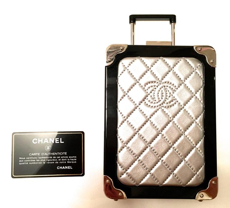 Presented here is an absolutely stunning runway purse from Chanel. Theclutch/purse is a mini version of a carry-on bag. There is a small retractable handle and small wheels just like a normal full-size carry-on piece of luggage. There is a shoulder