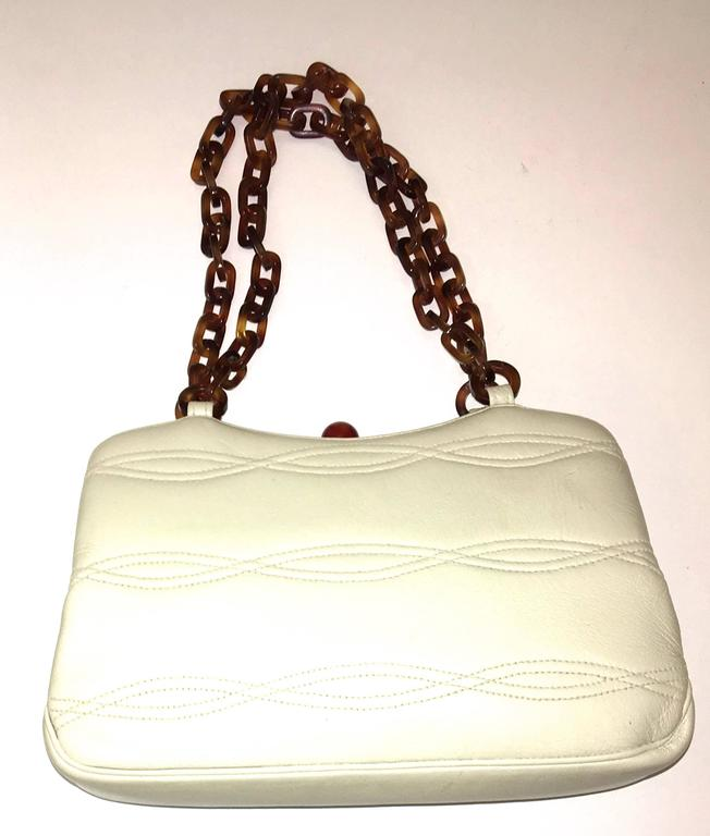 Presented here is a beautiful purse produced by Morris Moscowitz Co. The bag is from the 1950's. The purse has beige leather on the exterior of the bag with curved interlocking lined stitching on the exterior of the bag. The bag is entirely lined