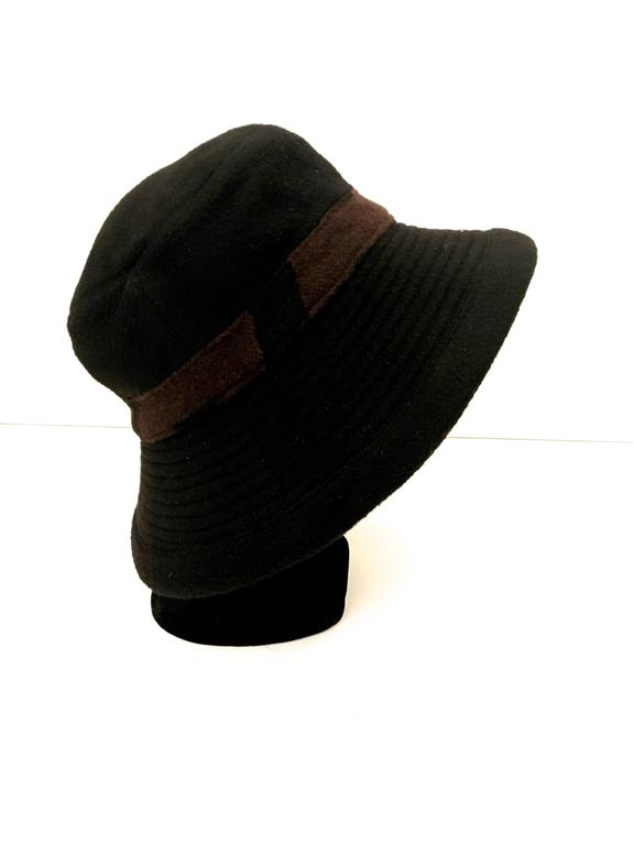 Presented here is a beautiful hat from Hermes Paris. This beautiful black hat is made from 100% camel's hair. There is a brown and black patterned band around the crown of the hat. The hat can be worn down or with the brim up. When worn down, the