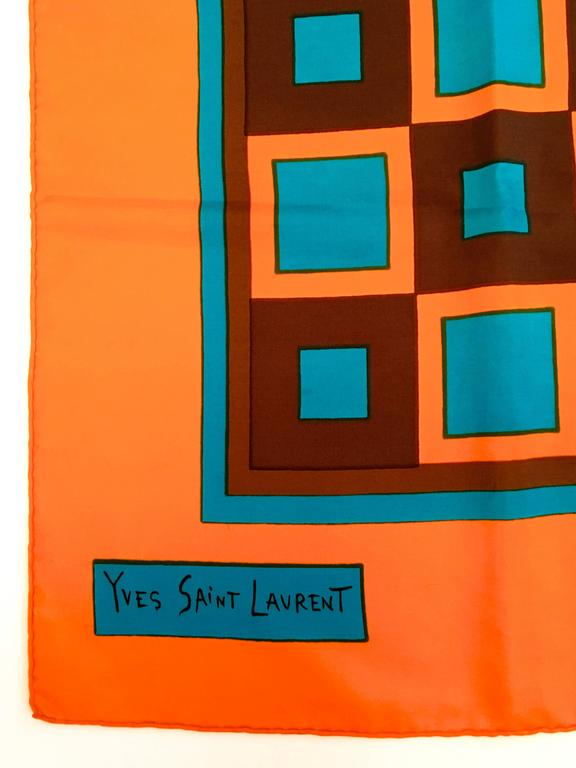 Presented here is a beautiful scarf from Yves Saint Laurent (YSL.) This hand rolled scarf is made from 100% silk. The scarf is from the 1980's. The design of the scarf is a composition of orange, brown and blue squares in a gridded almost