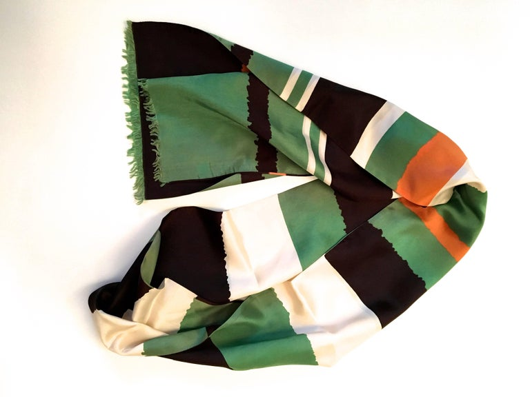 Presented here is a beautiful vintage scarf from the 1960's. This scarf is comprised of colors of orange, green, black and white. The colors are each illustrated in a series of thick solid color bars that stretch down the length of the scarf. The