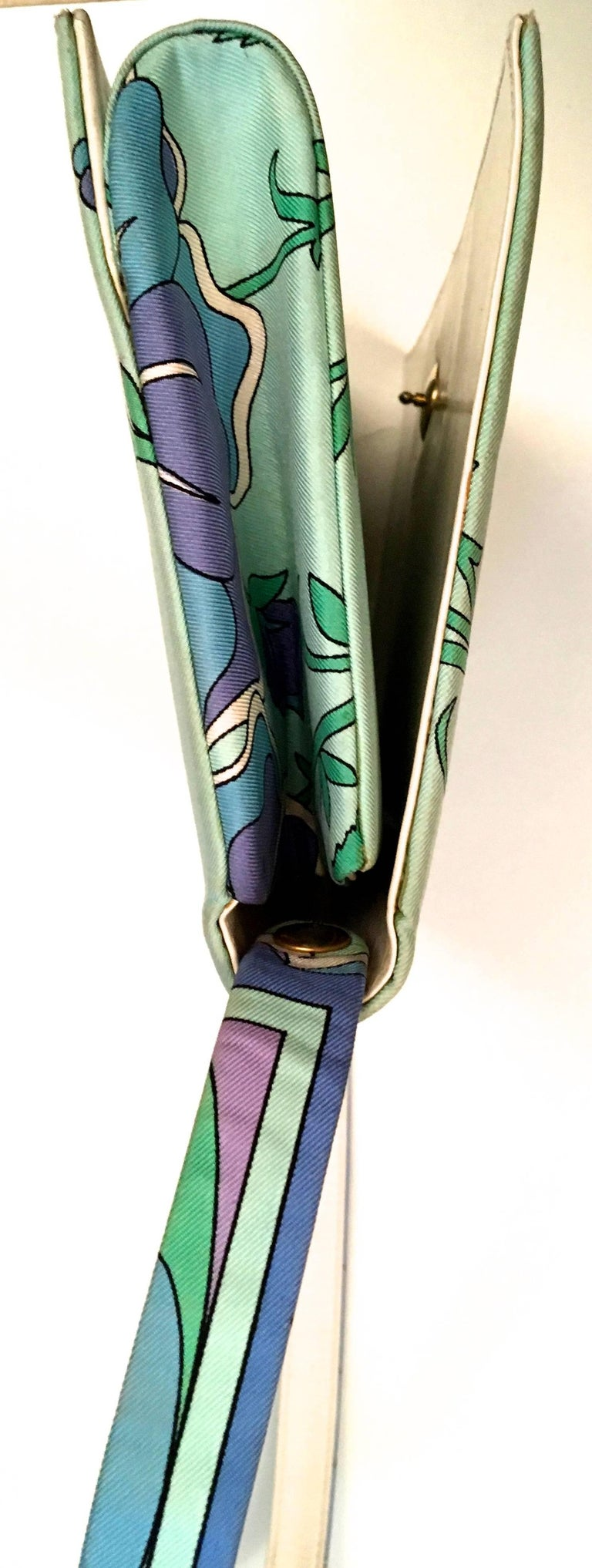 Presented here is a vintage handbag from Emilio Pucci. This vintage handbag is from the 1960's. The bag is near mint condition with images of flowers of green, lavender and light blue. The print design is distinctively Pucci styling. The bag is made