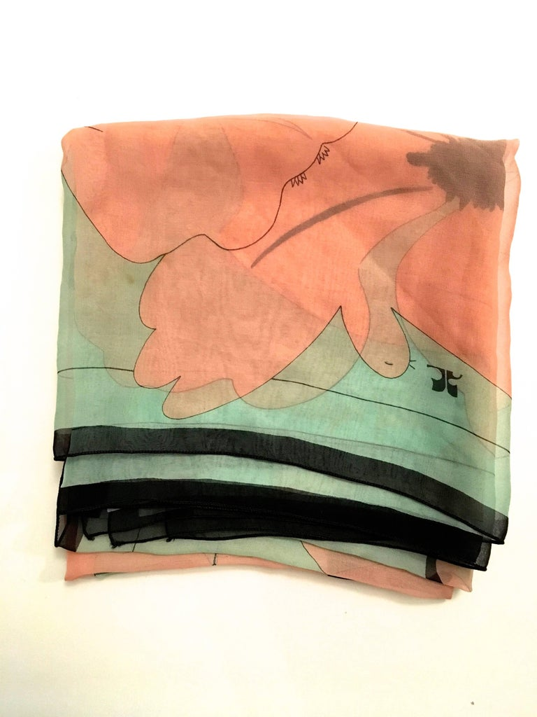 Presented here is a scarf from Courreges Paris. This beautiful scarf is made from 100% silk musselin. The scarf is a floral print and is comprised of pink and black colored flowers against a light blue background. The images are all framed by a
