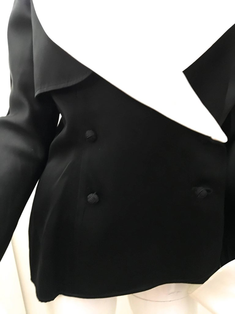 Presented here is a fabulous dinner jacket from Jean Louis Scherrer. This stunning jacket is comprised of an ultra soft black acetate with a removable white cuffs and collar. There is a delicate soft sheen that creates a beautiful look when the