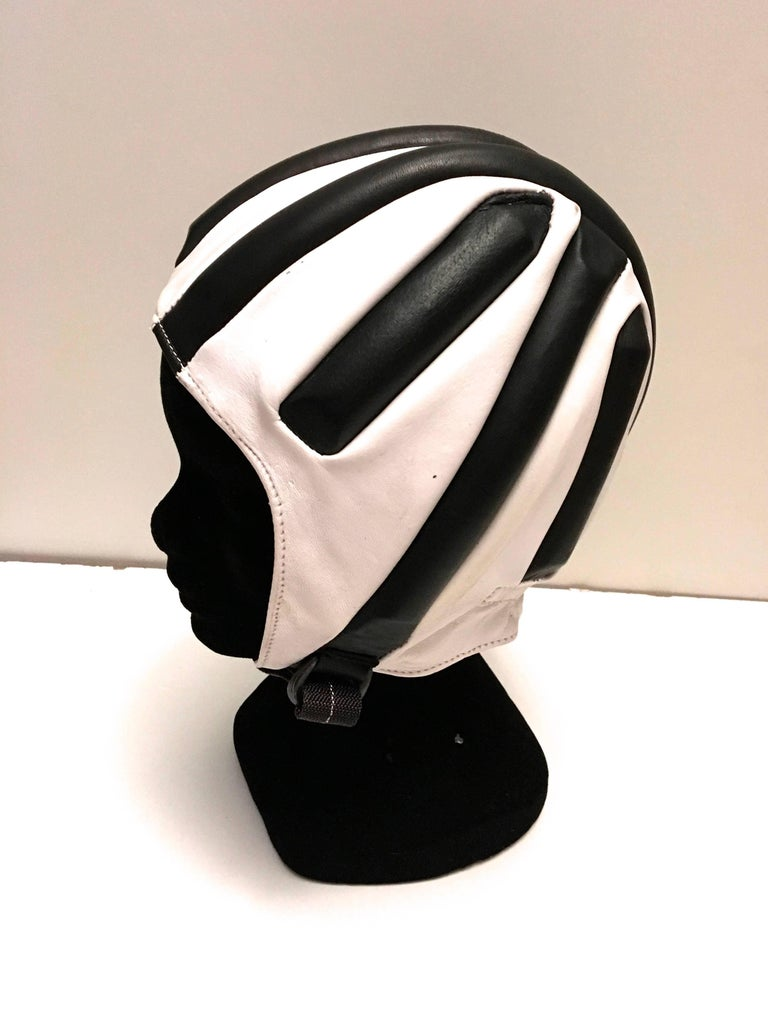 Presented here is a racing cap / helmet from the Italian manufacturer, Boeri. This fantastic helmet appear to have never been used. It still has its original box. The helmet is comprised of black and white leather with protective padding built