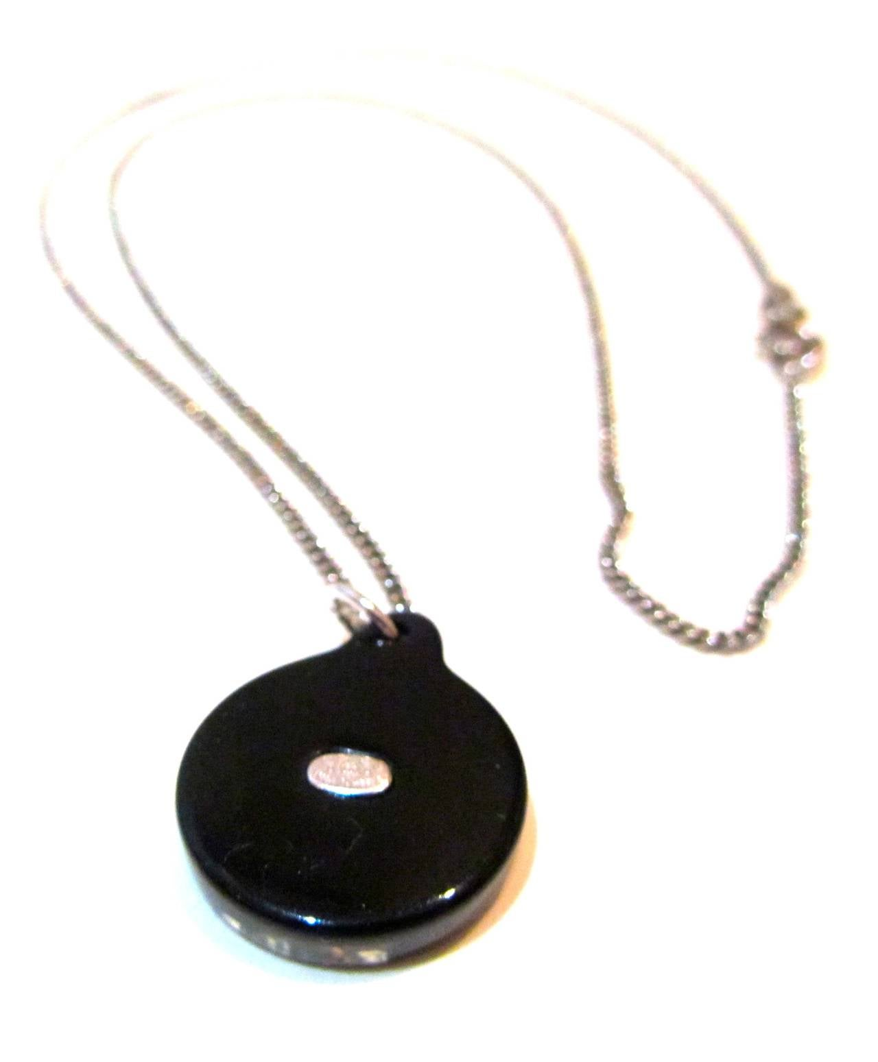 Beautiful Chanel necklace made of black and clear resin. Embedded in the charm is a crystal Chanel CC logo. The chain of the necklace has a silver tone and measures a total of 24 inches. The charm itself is 0.6 inches in diameter. 