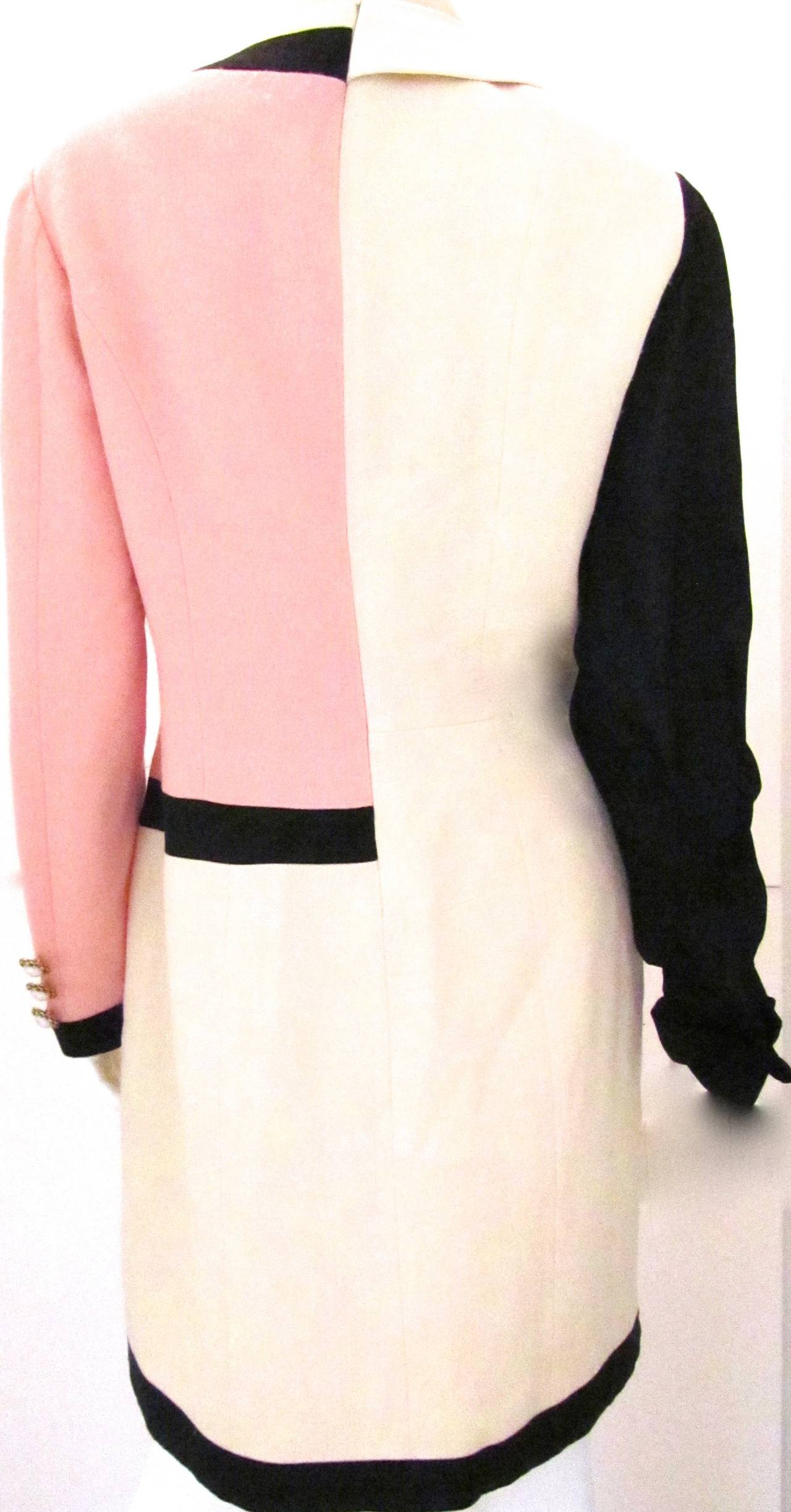 Moschino wool crepe runway dress from 1996. Half of the dress is a pink jacket in the style of Chanel. The other half of the dress is white with a  Peter Pan styled bow at the top. Black trim along is along center of the front, the neckline, the