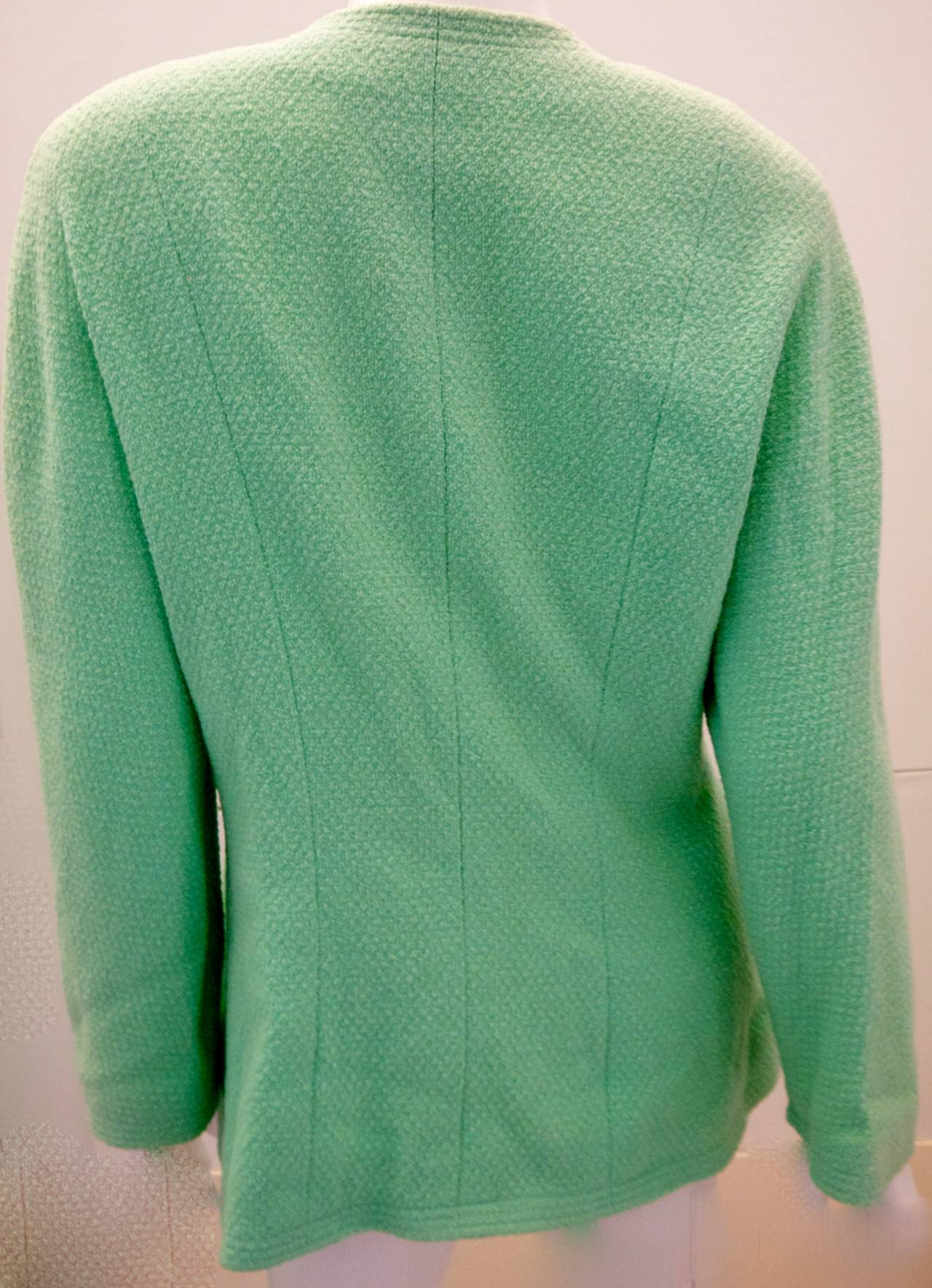 Gorgeous Chanel Boutique sea foam green jacket from the early 1980's. The jacket is in near mint condition and is a size 42. The jacket has dark charcoal gray buttons along the front and 4 large pockets along the front of the jacket. The jacket is