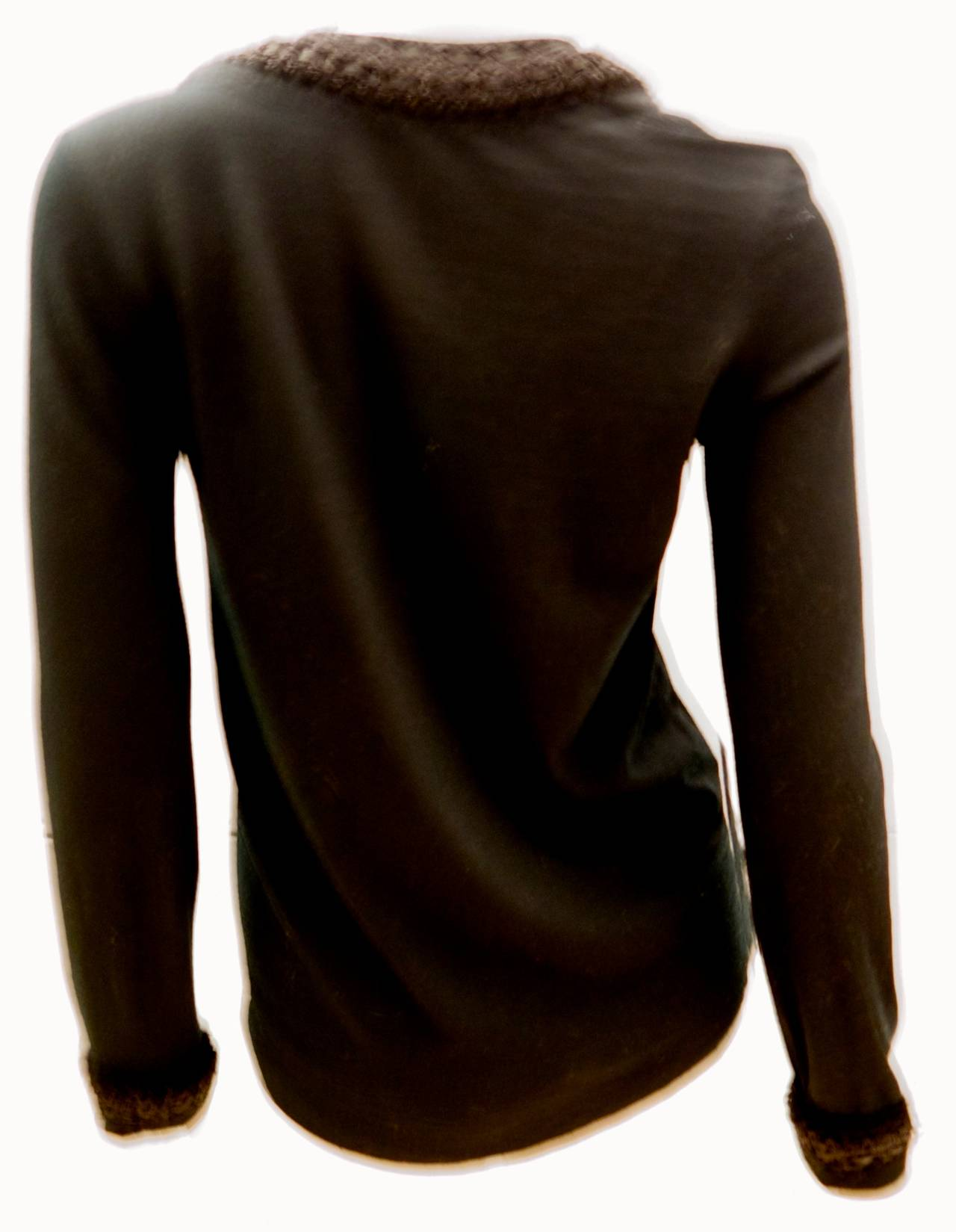 Chanel black shirt. The collar is a very intricately woven design comprised of lambskin and nylon. The collar of this shirt makes this shirt is a simple yet elegant masterpiece of fashion by Chanel. There is a small CC emblem below the color on the