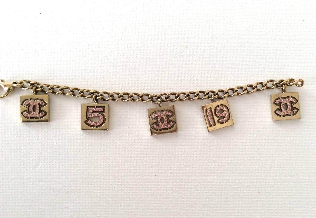 This is a very fun vintage Chanel charm bracelet which consists of 5 charms with pink rhinestones on both sides of the bracelet. 3 of the charms have the CC logo on them. One of the charms is the number 5 and one of the charms is the number 19. It