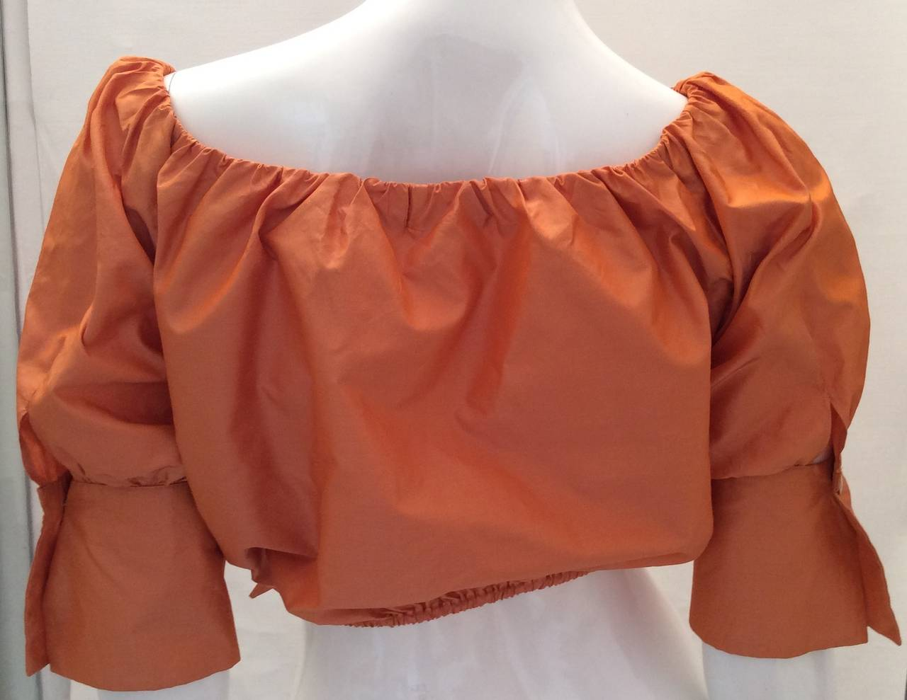 This beautiful orange 100% silk Max Mara evening top has elastic around the top which makes it as beautiful off the shoulder as it is on the shoulder. It has a front tie closure and above the front tie enclosure is a 4.5 inch opening which you don't