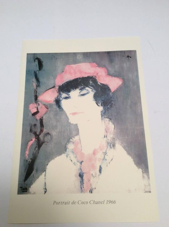 Here is a print of an oil portrait of Coco Chanel from the 1960's. The image is Coco dressed in white and pink against a charcoal background. A remarkable portrayal of the fashion icon. It is a print on professional art card stock printed in color.
