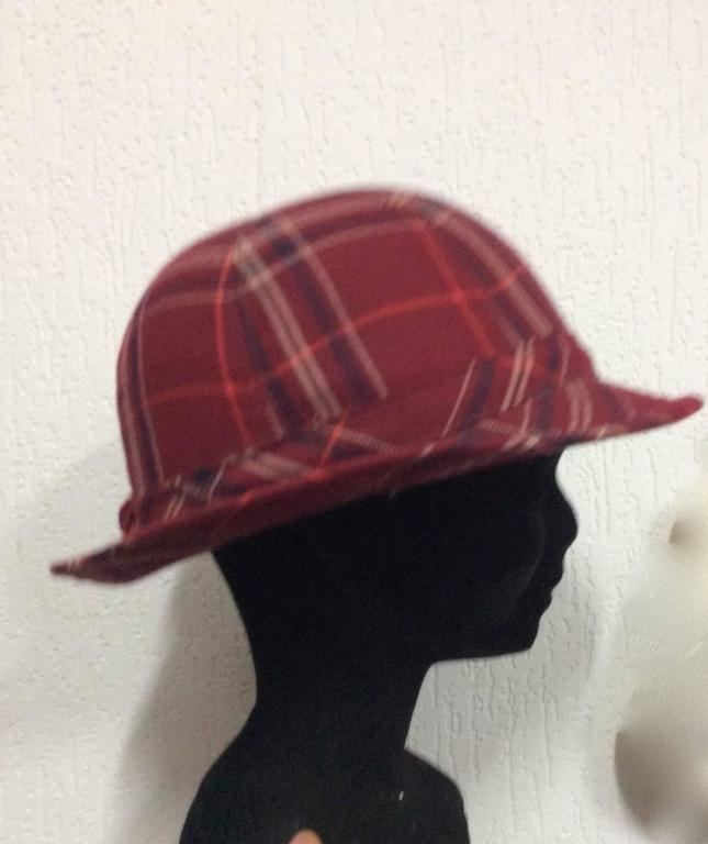 This adorable 1970's plaid hat has an inner circumference of 21 inches. The brim of the hat measures 1.75 inches. It is in excellent condition. The beautiful wool plaid has a combination of red, blue, white, and orange stripes.