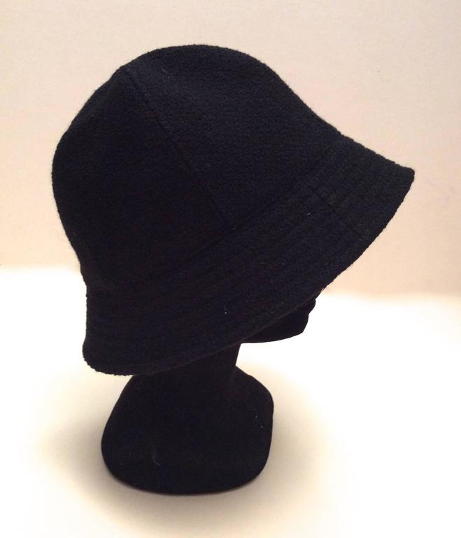 Here is a magnificent Chanel hat that is made of black boucle fabric. It is size 57 is adorned with a gray silver tone metal camellia emblem on the exterior of the hat. There is a 2.1 inche rim around the exterior of the hat. There is 8.5 inches of