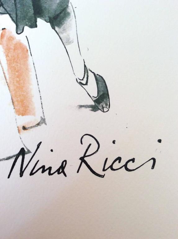 This is a print of a fashion advertisement for Nina Ricci from the 1960's. The print is a beautiful image of a woman in a dress surrounded by picture frames and canvases. One of the canvases has a city backdrop in the background of the picture. The