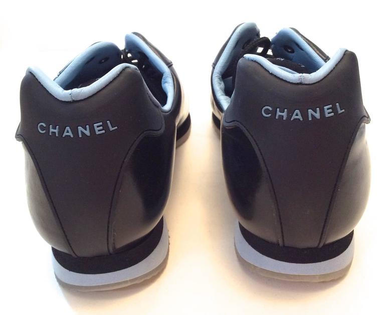 New Chanel black sneakers that are size 35.5 They are a beautifully designed shoe with the CC branding on exterior of the shoe. They have a gridded lined sole and are signed throughout the body of the shoe. A rare and difficult shoe to find that