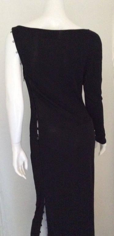 Presented here is a fabulous Gianfranco Ferre dress. The dress is a long, black dress made out of silk jersey. The dress has one size and the other side is sleeveless with articulate loops that button shut going up the side of the dress. The dress