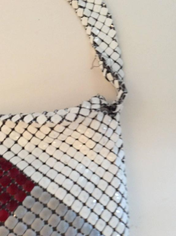 This metal bag is beautifully colored in white, red, and silver. It is extremely rare and one of the earliest examples of Bottega Veneta that I've ever seen. The condition is okay, but the metal has separated in two different places which is visible