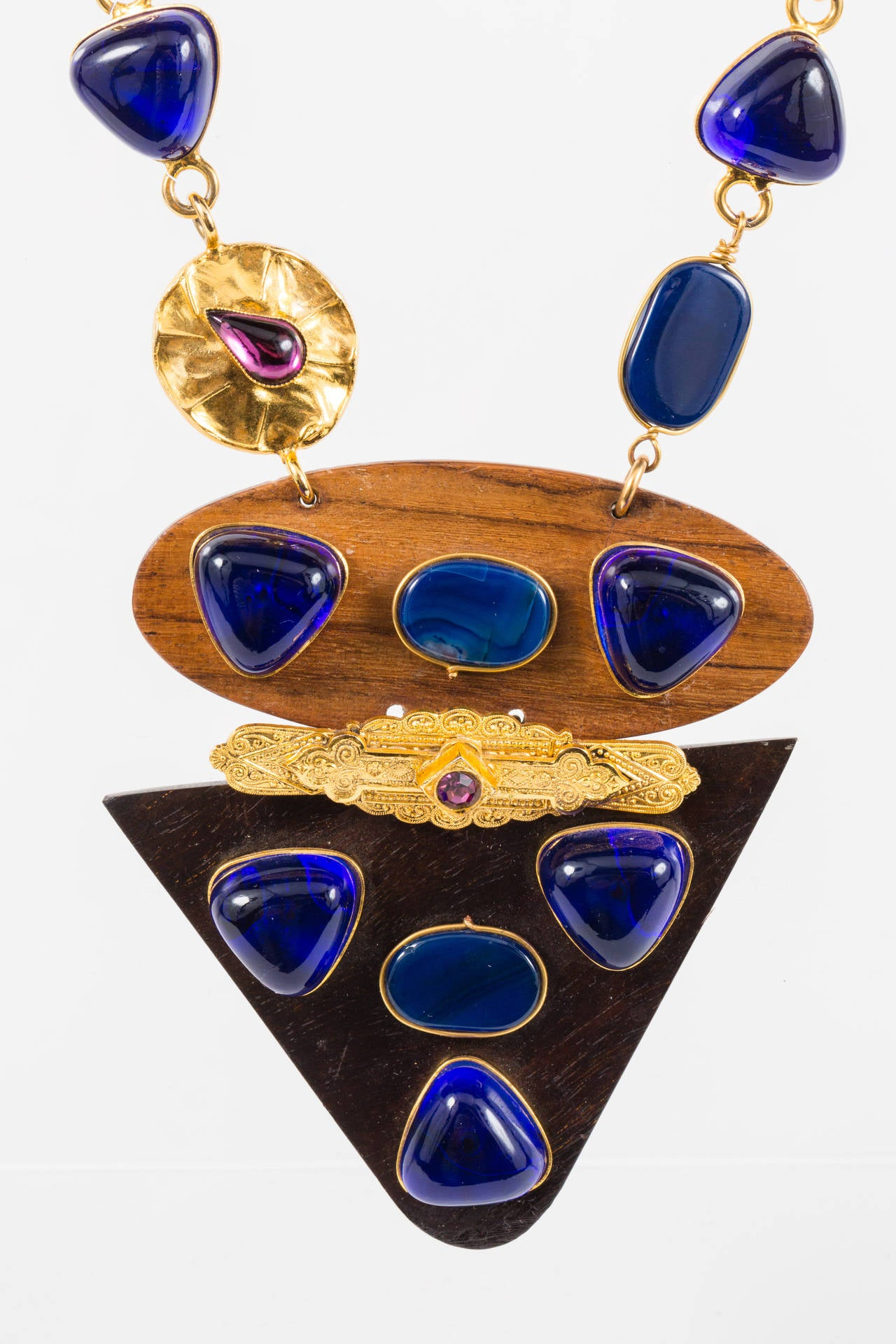 Exceptionally strong piece, this necklace is made of an interesting mix of materials and has the YSL logo plaque on the back clasp. Two types of wood compose the front pendants, which are accentuated by cobalt blue poured glass stones through out.