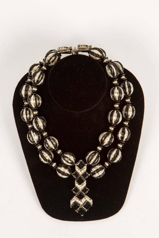 A real showstopper, this Art Deco inspired necklace, a revival look popular in the 1970's, with the look of onyx and crystal set in silvered metal.  Round metal beads are covered in both black and clear crystal beads and there are rhinestones