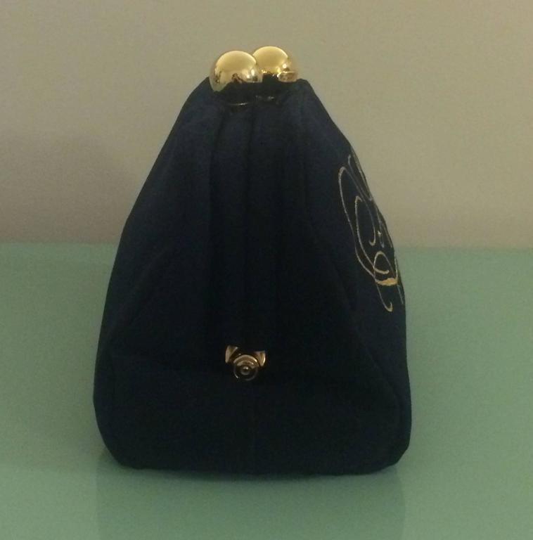 Moschino Redwall 1990's super-soft black clutch reads 'Soft!' in curling gold embroidery. Signed 'Moschino at gold ball on top.' Hinge closure (kisslock at top is decorative.)  Large main compartment and small interior zippered pocket.  Made in