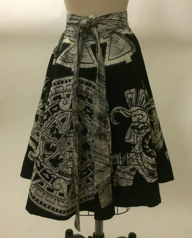 Black full skirt encircled with white Aztec calendar & warriors. Two short straps from the back panel wrap around the waist and fasten with two hook and eye closures, while two longer straps attached to the front panel tie over them to conceal