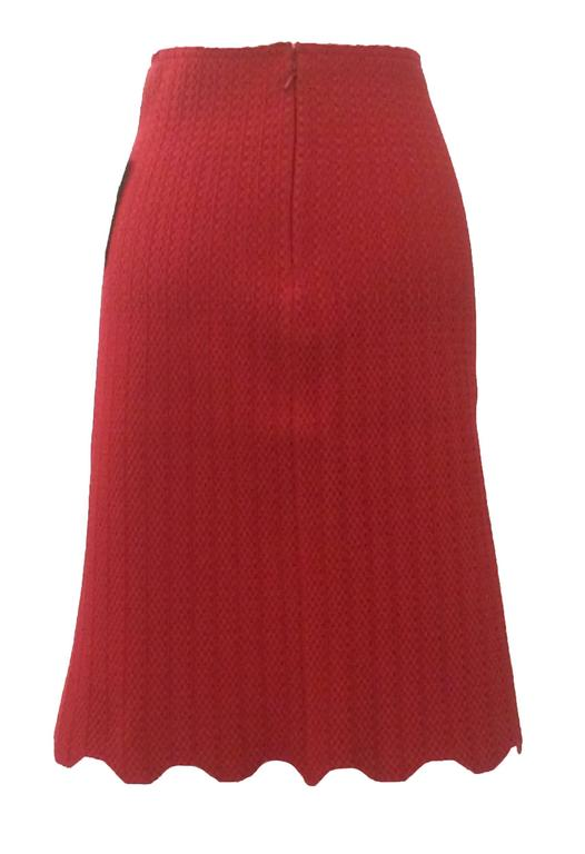 Deep red Alaia stretch knit skirt with an amazing stretchy texture, vertical detailing, and scalloped hem. Back zip and hook and eye.  Made in Italy.  Size 36, fits like S. Measurements taken unstretched, skirt is very stretchy. Waist