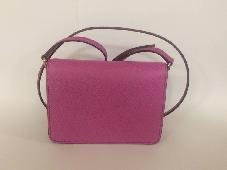 Dolce & Gabbana purple pink textured leather cross body bag with front flap closure. Magnetic front snap, card slot beneath flap and at inner bag. Adjustable strap.  Signed 'Dolce & Gabbana, Milano, Italia' at front