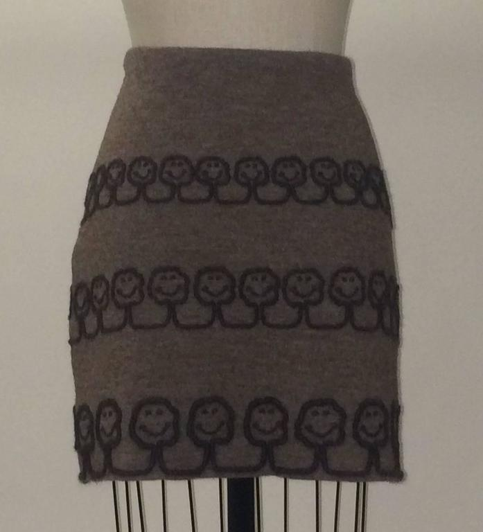 Moschino light brown knit skirt with dark brown smiling trees appliquéd in yarn from Moschino's 'Nature Friendly Garment' line. Fully lined, side zip.  100% wool. Fully lined in 100% rayon.   Made in Italy.  Labelled size IT 42, US 8. Runs