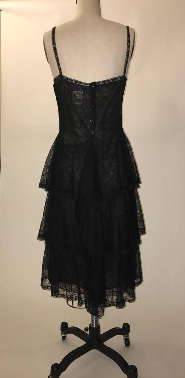 Chanel semi-sheer nude dress with black floral lace overlay from the 2000 collection. Scalloped detail at waist. Scattered sequins at lace trim.  Lace straps. Back zip at lining with CC logo buttons that conceal it on the lace overlay.  Retailed