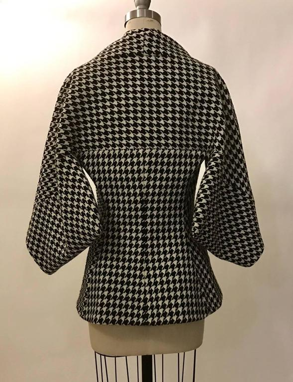 Alexander McQueen black and white dogtooth wool jacket from the 2009 Horn of Plenty collection. Jacket features a kimono like sleeve and pleat detail at shoulder. Fastens with three concealed buttons at front.   100% virgin fleece wool. Fully lined