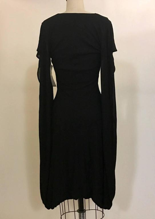 Alexander McQueen 2009 fitted black jersey v neck dress. A short bat-wing sleeve extends all the way down and connects to the draped skirt. Slight bubble hem. A true piece of cutting and draping genius!  100% rayon.  Made in Italy.  Labelled size IT